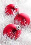 Red christmas baubles. Tree red glass Christmas baubles close up among white shiny tinsel Stock Images