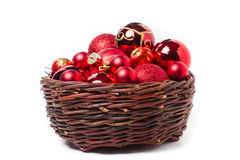 Red christmas baubles in wicker basket Royalty Free Stock Photos