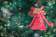 Christmas bell with text merry Christmas and Christmas tree background. Xmas theme stock photos