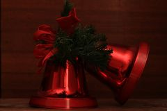 Red Christmas bells. On a wooden table royalty free stock photography