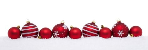 Red christmas big and small balls isolated on snow stock images