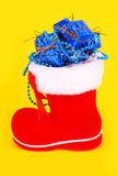Red Christmas boot with gifts. Red Christmas boots with gifts on a yellow background Royalty Free Stock Photography