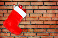 Red christmas boot with gifts on background brick Royalty Free Stock Images