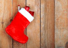 Red christmas boot with gifts on background wooden Stock Images