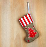 Red christmas boot with gifts on  wooden wall Royalty Free Stock Photo