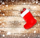 Red christmas boot with gifts on wooden wall Stock Image