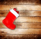 Red christmas boot with gifts on wooden wall Stock Photo