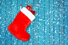 Red christmas boot with gifts on wooden wall Royalty Free Stock Photos