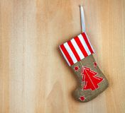 Red christmas boot with gifts on wooden wall Royalty Free Stock Photography