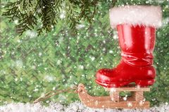 Red christmas boot on a sled. Christmas background Stock Photos