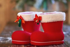 Red Christmas boot with white border and small bells on wooden table. royalty free stock images