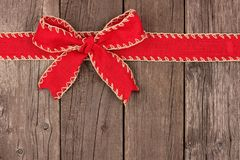 Red Christmas bow and ribbon top border on old wood. Rustic red Christmas bow and ribbon top border, above view on an old wood background Stock Image