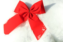 Red christmas bow on the snow Stock Photo