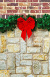 Red Christmas bow on stone fence Royalty Free Stock Photo