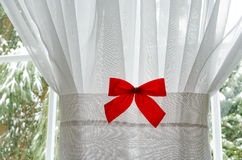 Red Christmas Bow on White Window Curtain 2. Red Christmas Bow on White Window Curtain with a glimpse of window panes and snow covered trees outside Stock Images