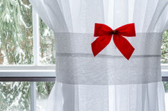Red Christmas Bow on White Window Curtain. Loking outside towards snow covered trees Royalty Free Stock Photography