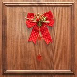 Red christmas bow on a wood. En surface with wood border Stock Images