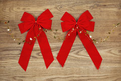 Red Christmas Bows and Golden Stars on Faded Wood. Overhead view of Christmas red bows and golden stars on string positioned on rustic wooden boards stock photo