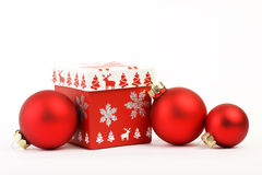 Red christmas box with red Christmas decoration and three red matt christmas balls on white background. Christmas box with christm Royalty Free Stock Images