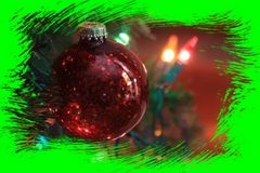 A Red Christmas Bulb shot closeup. On a Christmas tree with Christmas lights by a window and a curtain. With a Green frame around the Christmas bulb Stock Photo