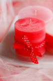Red Christmas candle. With a ribbon in polka dots on a white background Royalty Free Stock Photography