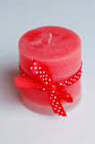 Red Christmas candle. With a ribbon in polka dots on a white background Royalty Free Stock Photos