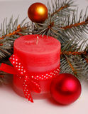 Red Christmas candle. And Christmas tree branch with decoration Stock Photo