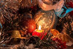 Red Christmas candle on the background of New Year`s decorations and a bell. The magic of Christmas and New Year Stock Image