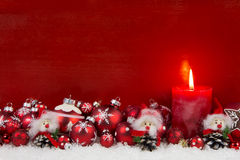 Red christmas candle with balls and imp on wooden background. Royalty Free Stock Photo