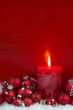 Red christmas candle with balls on wooden background. Royalty Free Stock Photos