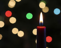 A Red Christmas Candle with Blurred Lights Stock Photo