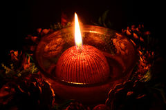 Red christmas candle burning on a black background Stock Photography