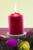 Red Christmas candle burning. Decorated by a fir branch and rose petals Stock Photo