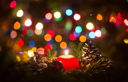 Red Christmas candle with Christmas lights blurred. Christmas candle and Santa Clouse surrounded with pine branches and Christmas lights blurred in the Royalty Free Stock Images
