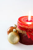 Red Christmas candle and Christmas ornaments. On white background Stock Photography