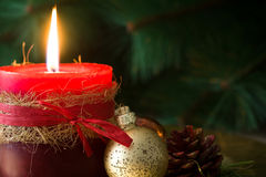 Red Christmas candle and Christmas ornaments. On wood Royalty Free Stock Photos