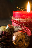 Red Christmas candle and Christmas ornaments. On wood Royalty Free Stock Image