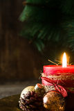 Red Christmas candle and Christmas ornaments. On wood Stock Images