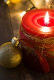 Red Christmas candle and Christmas ornaments. On wooden background Stock Images
