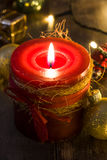 Red Christmas candle and Christmas ornaments. On wooden background Stock Photo
