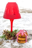 Red Christmas candle with fir branches and cones in winter. Red Christmas candle with fir branches and cones and oat cookies on the old wooden table in winter Stock Photos