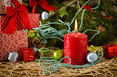 Red christmas candle gifts pine cones flame. On a colored background Stock Photography