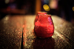 Red Christmas candle lantern. On the wooden table with water drops Royalty Free Stock Images
