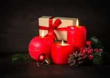Red christmas candle. Present and decorations on dark background Stock Photo