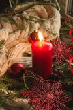 Christmas candle. Red Christmas candle with red snowflakes, knitting scarf Stock Images