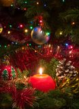 Red Christmas candle surrounded by pine branches and balls Stock Photo