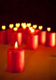 Red Christmas candle on table. With group of similar candles with hearts for flames on background Stock Photo