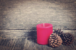 Red Christmas candle. And three pine cones on wooden table with vintage and vignette tone Stock Photography