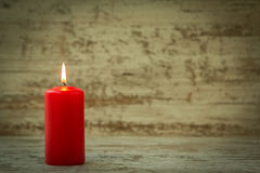 Red Christmas candle. On a white wooden background Royalty Free Stock Photography