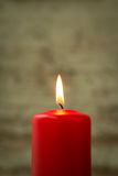 Red Christmas candle. On a white wooden background Royalty Free Stock Image